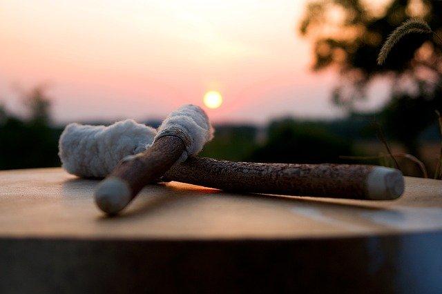 2 maillets sur un tambour avec un coucher de soleil